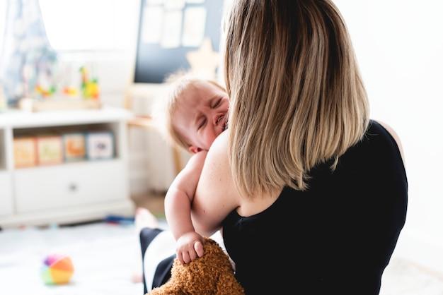 Zurück von einer mutter, die ein schreiendes baby trägt Premium Fotos