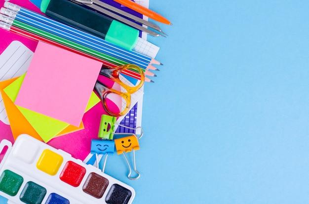 Zurück zu schule mit schulzubehör - farben, bleistifte, notizbücher, scheren, markierungen, blauer hintergrund. Premium Fotos