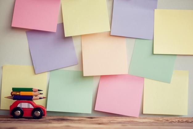 Zurück zu schulhintergrund mit rotem miniaturauto tragen bunte bleistifte über bunten stikers an der wand. Premium Fotos