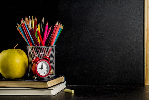 Zurück zu schulkonzept mit buchweckerfarbe zeichnet tafelhintergrund an Premium Fotos