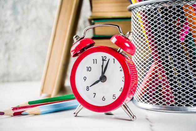 Zurück zu schultabelle mit alten büchern, wecker, bleistiften Premium Fotos