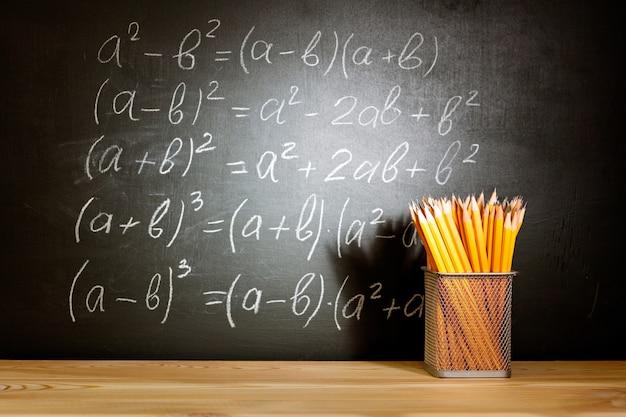 Zurück zum schulkonzept. alte schulbücher und bleistifte, die auf einer hölzernen schulbank vor einer schwarzen tafel mit schule der mathematischen formeln liegen. Premium Fotos