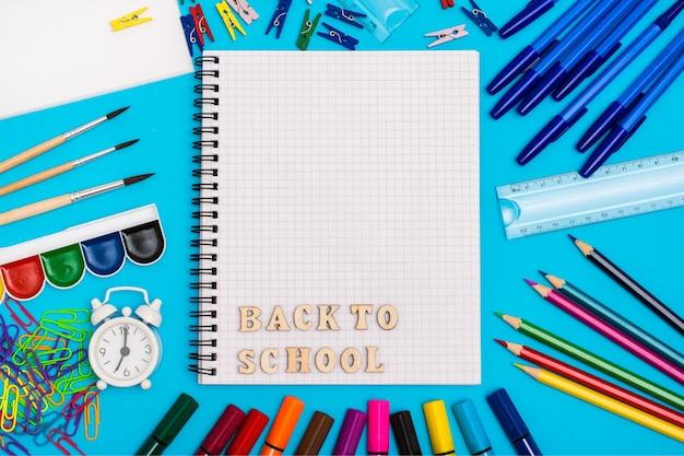 Zurück zur schule. briefpapier, wecker und inschrift in den hölzernen buchstaben in einem notizbuch auf einem blauen hintergrund. draufsicht Premium Fotos