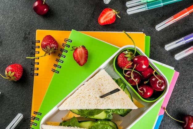 Zurück zur schule. eine herzhafte gesunde schulmahlzeit in einem kasten: sandwiche mit gemüse und käse, beeren und früchten (äpfel) mit notizbüchern, farbstifte auf einer schwarzen tabelle. Premium Fotos