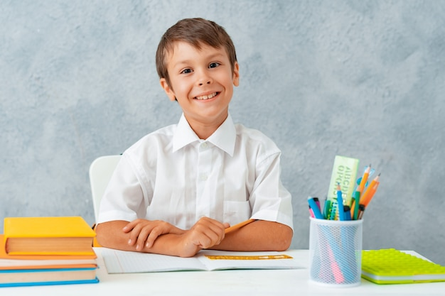Zurück zur schule. glücklicher lächelnder student zeichnet am schreibtisch. Kostenlose Fotos