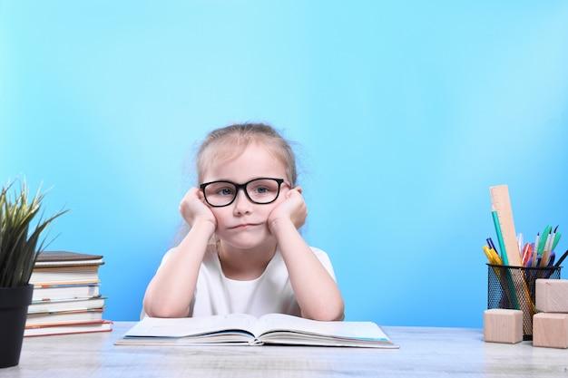 Zurück zur schule. glückliches süßes fleißiges kind sitzt drinnen an einem schreibtisch. kind lernt im unterricht. Premium Fotos