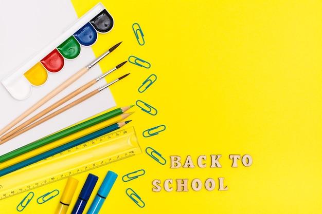 Zurück zur schule. malutensilien und inschrift in holzbuchstaben auf gelbem grund. draufsicht Premium Fotos