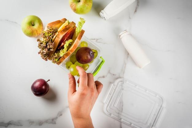 Zurück zur schule. person, die gesunde brotdose mit äpfeln, pflaumen, trauben, joghurt, sandwichkopfsalat, tomaten, käse, fleisch der frischen frucht macht. weißer marmortisch. draufsicht weibliche hände Premium Fotos