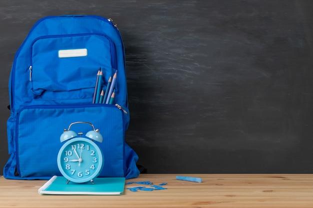 Zurück zur schule. rucksack, wecker und bücher himmelblauer ton auf klassenzimmerschreibtisch mit tafelhintergrund. Premium Fotos