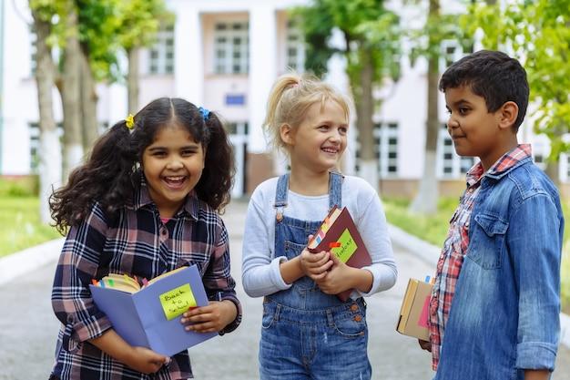 Zurück zur schule. schließen sie herauf drei freunde mit den rucksäcken, die vor schule umarmen und lachen. gemischte rassengruppe von schulkindern, die spaß auf dem schulhof haben. Premium Fotos
