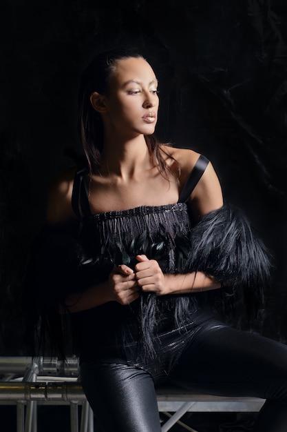 Zurückhaltendes porträt des hübschen mädchens in der pelzweste und in den lederhosen auf dunklem hintergrund Premium Fotos