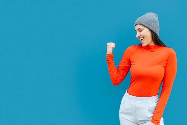 Zusammenpressende fäuste der glücklichen frau, die strickmütze mit kopienraum tragen Kostenlose Fotos