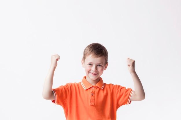 Zusammenpressende faust des glücklichen jungen, die ja geste auf weißer wand macht Kostenlose Fotos