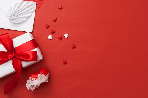 Zusammensetzung am valentinstag. geschenk, umschlag, herz und herzen. rote und weiße kombination mit Premium Fotos