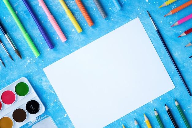 Zusammensetzung der malgeräte. bleistifte, marker, pinsel, farben und papier. blauer hintergrund Kostenlose Fotos