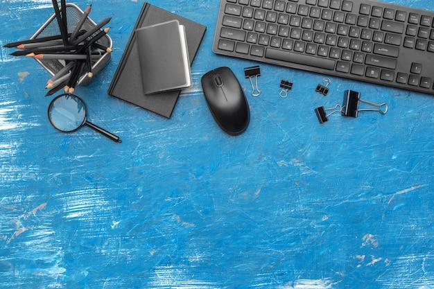 Zusammensetzung des büroartikels und der ausrüstung im schwarzen und blauen hintergrund, draufsicht Premium Fotos