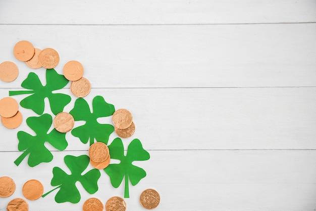 Zusammensetzung des haufens der münzen und des grünbuchklees an bord Kostenlose Fotos
