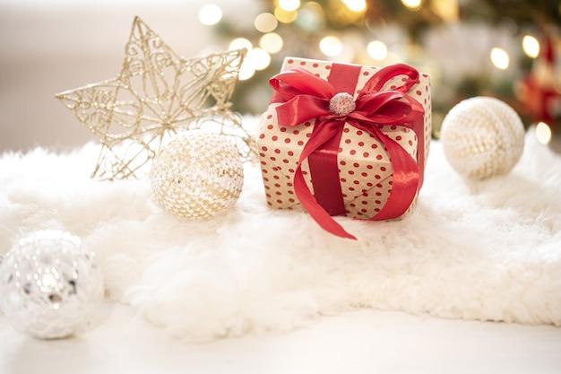 Zusammensetzung eines weihnachtsgeschenks und der neujahrsdekoration auf einem hellen hintergrund mit gerlandenlichtern. Kostenlose Fotos
