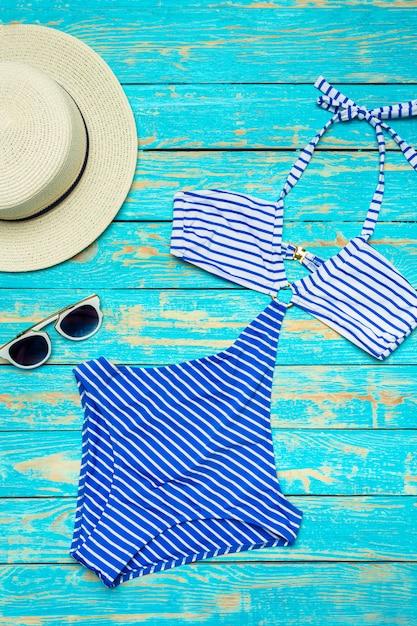 Zusammensetzung mit badeanzug auf farbhölzernem hintergrund Premium Fotos