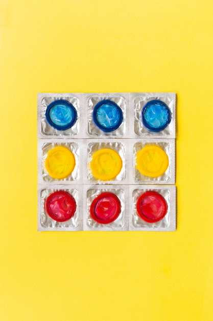 Zusammensetzung mit bunten kondomen auf gelbem hintergrund. safer sex und verhütungskonzept. flache lage, draufsicht, kopierraum. Premium Fotos