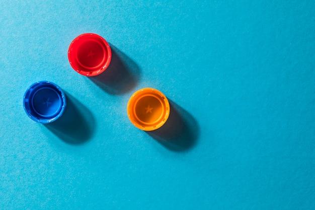 Zusammensetzung mit den plastikflaschen und kappen lokalisiert auf blau. Premium Fotos