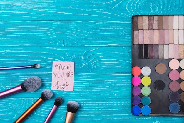 Zusammensetzung mit einem satz von make-up und notiz für muttertag Kostenlose Fotos