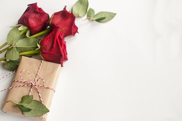 Zusammensetzung mit geschenk und blumenstrauß von roten rosen auf weißem hintergrund Premium Fotos