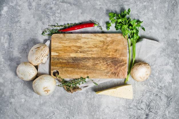 Zusammensetzung mit leerem hölzernem brett und gemüse auf küchentisch Premium Fotos