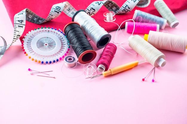Zusammensetzung mit threads und nähendem zubehör auf rosa hintergrund Premium Fotos