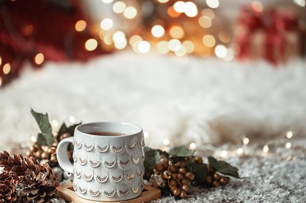 Zusammensetzung mit weihnachtsbecher mit heißem getränk auf unscharfem abstraktem hintergrund Premium Fotos