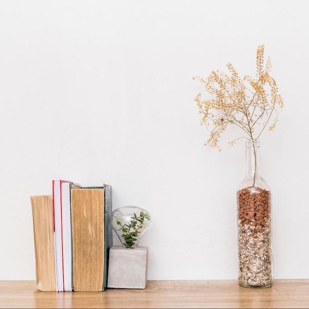 Zusammensetzung von getrockneten pflanzen und bücher auf dem tisch Kostenlose Fotos