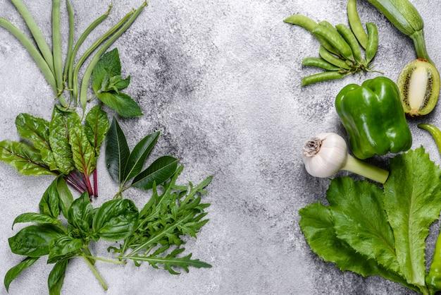 Zusammensetzung von hellem und saftigem grünem gemüse in der nähe von gewürzen und kräutern Premium Fotos
