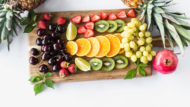 Zusammenstellung der früchte auf hackendem vorstand über weißem hintergrund Kostenlose Fotos