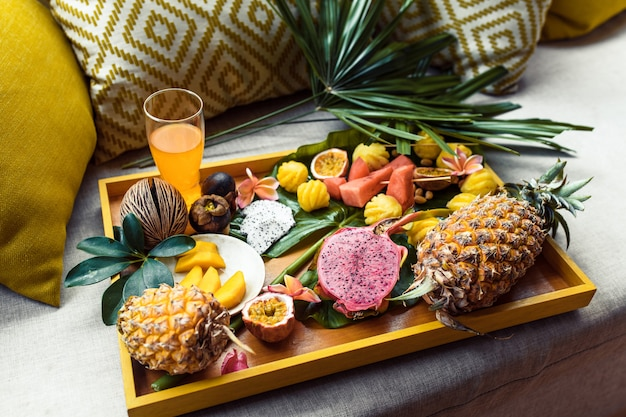 Zusammenstellung der tropischen früchte und frischer saft auf einem gelben behälter mit palmblatt. ansicht von oben. frühstück Premium Fotos