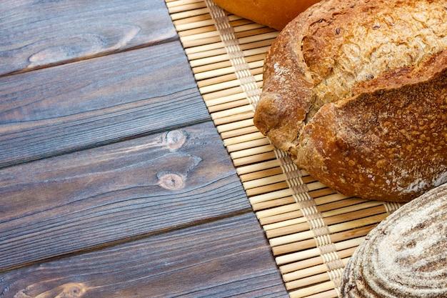 Zusammenstellung des gebackenen brotes auf hölzerner tabelle. draufsicht mit kopienraum Premium Fotos
