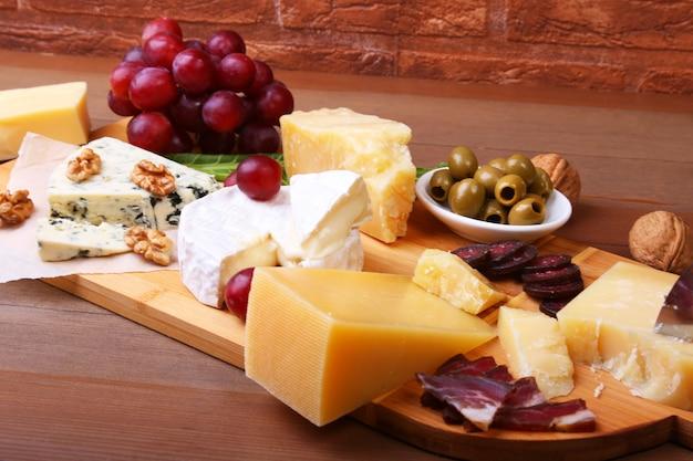 Zusammenstellung des käses mit früchten, trauben, nüssen und käsemesser auf einem hölzernen umhüllungsbehälter. Premium Fotos