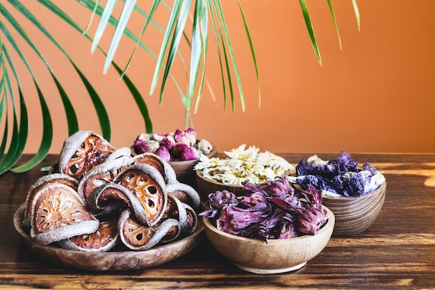 Zusammenstellung des trockenen gesunden tropischen kräutertees in den hölzernen schüsseln und im palmblatt auf rustikalem hintergrund. Premium Fotos