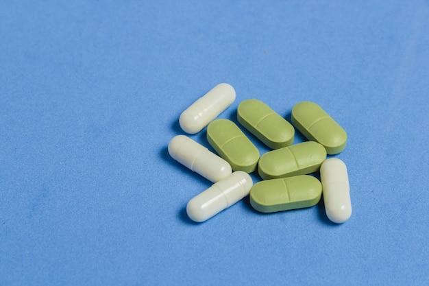 Zusammenstellung von pillen, von tabletten und von kapseln auf blauer tabelle. Premium Fotos