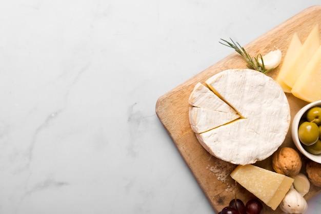 Zusammenstellung von verschiedenen köstlichkeiten auf hölzernem brett mit kopienraum Kostenlose Fotos