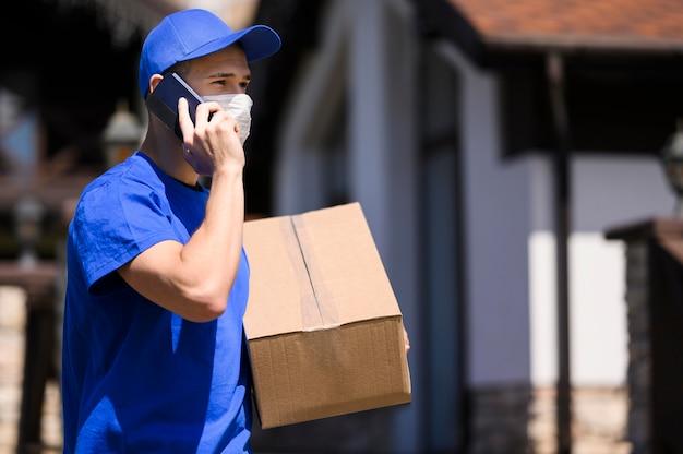 Zusteller mit gesichtsmaske, die paket trägt Kostenlose Fotos