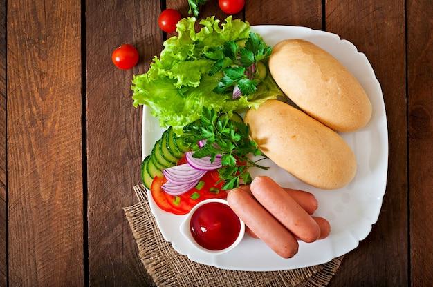 Zutaten für die zubereitung von hot dogs auf einem weißen teller Premium Fotos
