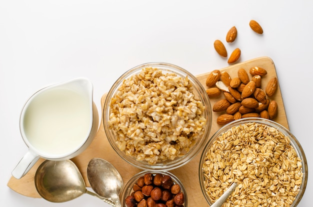 Zutaten für ein gesundes frühstück - haferflocken, milch und mandeln auf weiß Premium Fotos