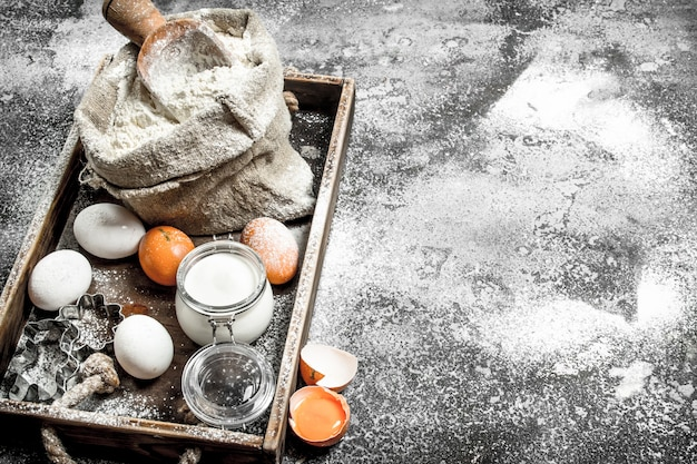 Zutaten für teig in einem holztablett auf rustikalem tisch. Premium Fotos