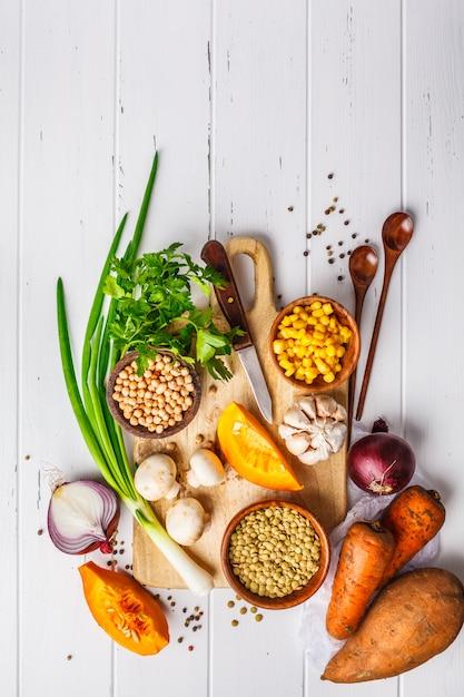 Zutaten für vegane gemüsesuppe mit linsen, pilzen und kichererbsen auf weißem hintergrund. Premium Fotos