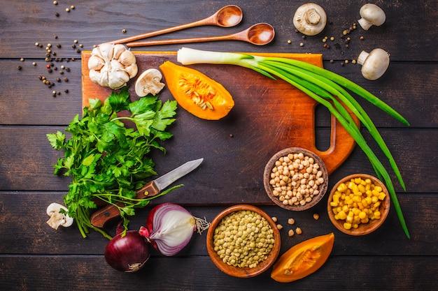 Zutaten für vegane gemüsesuppe mit linsen und kichererbsen auf dunklem holz Premium Fotos
