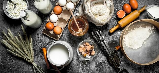 Zutaten und werkzeuge für die teigzubereitung auf rustikalem tisch. Premium Fotos