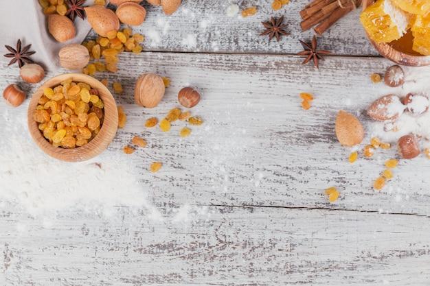 Zutaten zum kochen von brot oder keksen mit bienenwabe, mehl, rosinen, nussmischung, gewürzen Premium Fotos