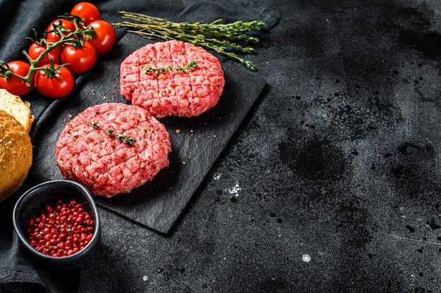 Zutaten zum kochen von burgern. hackfleischpastetchen, brötchen, tomaten, kräuter und gewürze. draufsicht Premium Fotos