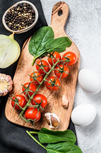 Zutaten zum kochen von shakshuka. eier, zwiebeln, knoblauch, tomaten, paprika, spinat. grauer hintergrund. draufsicht. Premium Fotos