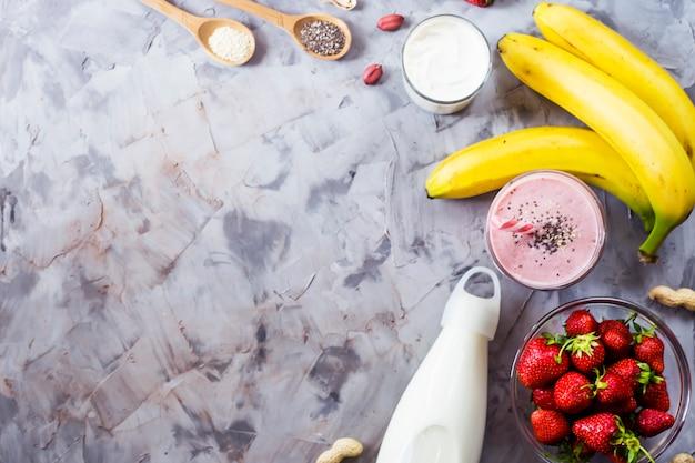 Zutaten zum kochen von smoothies aus erdbeeren, bananen, milch, joghurt Premium Fotos